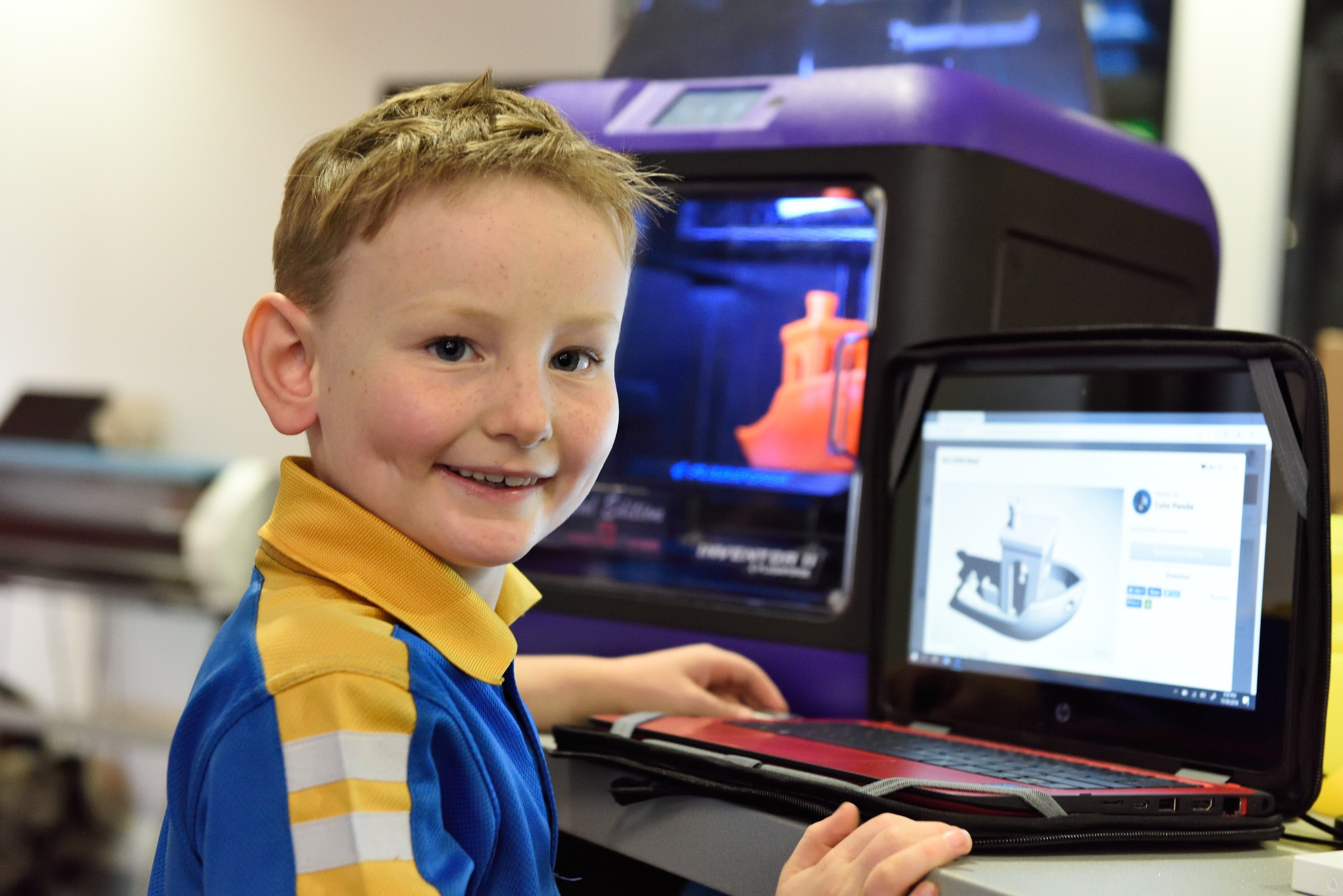 boy smiling in front of a laptop and 3D printer